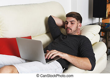 Young handsome man using his laptop on white couch Indoor