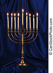 menorah - Gold menorah with lit candles on royal blue...