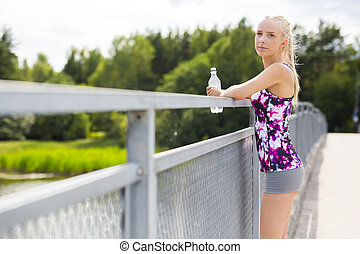 Exhausted young woman rests after stamina training