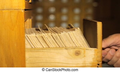 Reader looking for a book in the library card catalog -...