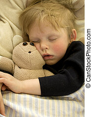 Cute sleeping child cuddling his teddy bear