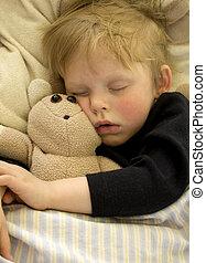 Cute sleeping child cuddling his teddy bear