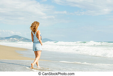Young woman in blue denim jumpsuit walking along beach and...