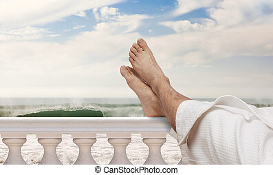 vacation feet - man wearing bathrobe resting feet on Italian...