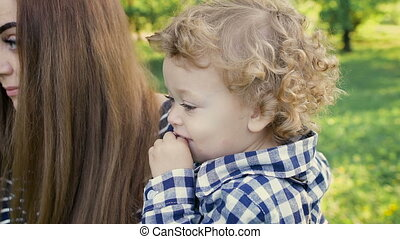Young beautiful mum holds on hands of his son's curly. She loves this little boy, kissing him on the cheek.