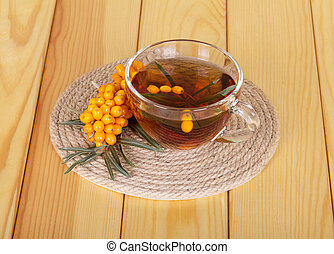 Bunch sea buckthorn and cup tea on background light wood -...