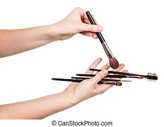 In womens hands set cosmetic brushes isolated on white - In...
