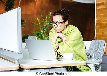 Beautiful thoughtful woman using laptop and feeling cold on...