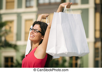 Woman shopping in european city - Joyful woman raising white...