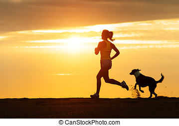 Woman and dog running on beach at sunset