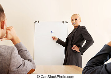 Smiling businesswoman drawing a graph for her colleagues on the whiteboard
