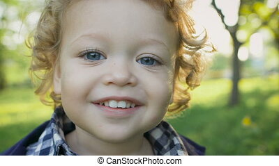 Portrait of a happy boy in the park malenkovo. Curious children with curly blond hair and blue eyes.
