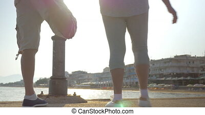 Man and Woman Stretching Leg Muscles - Low-angle shot of man...