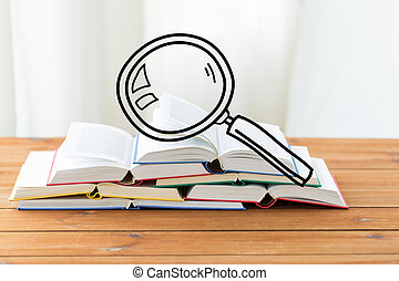 close up of books on table with loupe doodle - education,...