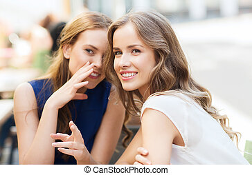 young women drinking coffee and talking at cafe - people...