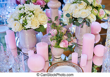 Table set for wedding reception with candles and flower bouquets