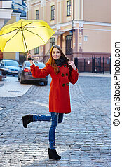young woman in a red coat with yellow umbrella walks through...