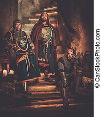 Medieval king with his knights in ancient castle interior
