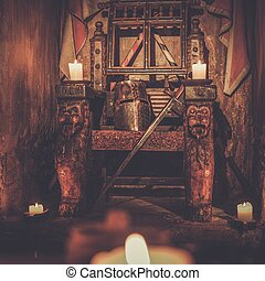 Medieval royal throne with helmet and sword in ancient castle interior.