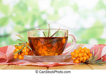 Ripe sea buckthorn berries and cup tea on abstract green -...