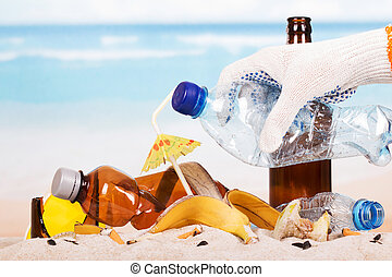 Hand holding plastic bottle on pile garbage in sand...