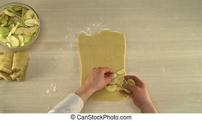 Putting sliced apples on kneaded dough - Cook putting sliced...