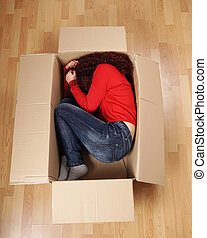 girl lying curled up in cardboard box - young woman lying...
