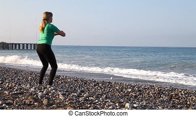 Young  woman is doing exercises on the beach