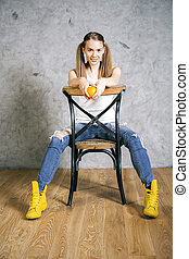 Girl on chair backwards - Pretty girl with ponytails holding...