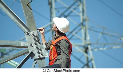 Electrical High Tension Pole Woman - Female technician in a...