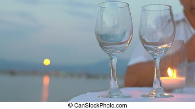 Pouring wine in glasses at seaside