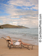 destressing - Young woman relaxing on a lounge chair near...