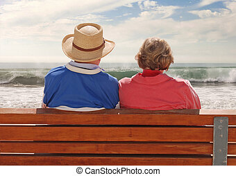 Golden Years - A senoir adult couple sitting at a benchand,...