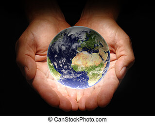 In His Hands - Hands holding the earth on a black background