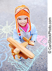 baby girl with wooden toy airplane on a background of children's