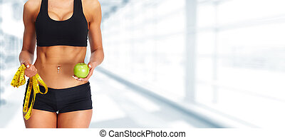 Woman abdomen with measuring tape and apple.
