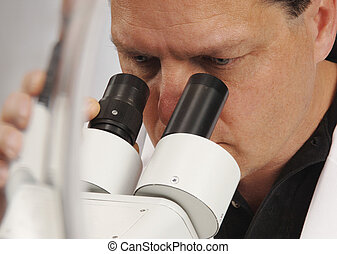 Microscopist - Closeup of a man looking into a microscope