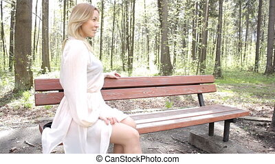 Beautiful, nice girl sitting on a bench in a park