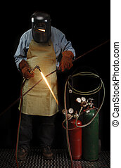 Welder Standing - Person in protective welding gear heating...
