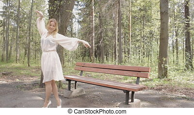 Young beautiful happy woman dances in park.