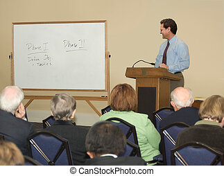 Lecture / Seminar - Man standing behind a podium, looking at...