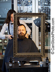 Man having his beard and hair trimmed at a barber -...