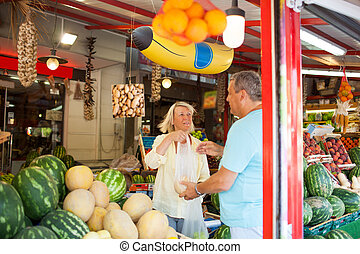 Couple shopping in a fruit and vegetable store - Middle-aged...