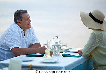 Middle-aged couple sitting waiting for a meal at a...