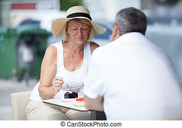 Elderly couple eating in outdoor cafe - Two tourists sitting...