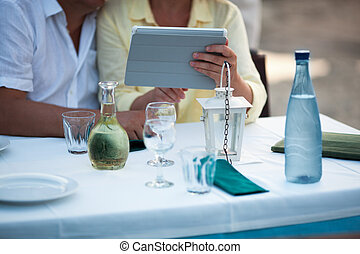 Middle-aged couple using a tablet at the table as they sit...