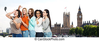 group of happy women taking selfie in london - friendship,...