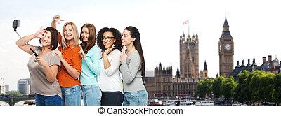 group of happy women taking selfie in london - friendship,...