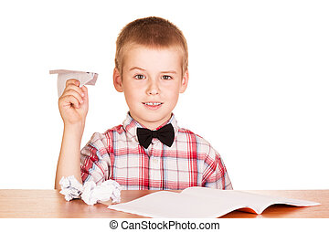 Boy sitting at table and make paper planes isolated - Cute...