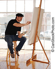 Studio Artist - Artist painting on canvas in studio wearing...